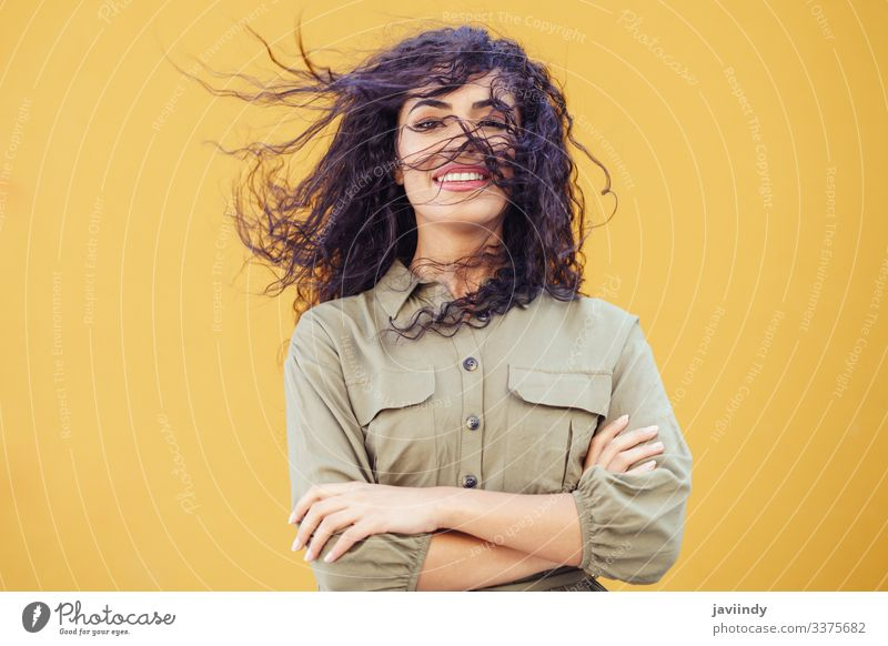 Arab Woman with curly hair in her face woman arab hairstyle smile beautiful girl beauty young one fashion female arabic copyspace middle eastern yellow green