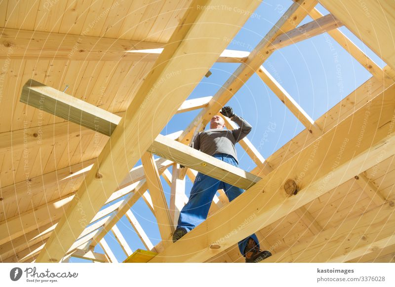 Builder at work with wooden roof construction. House (Residential Structure) Work and employment Craftsperson Construction site Industry Tool Hammer Human being