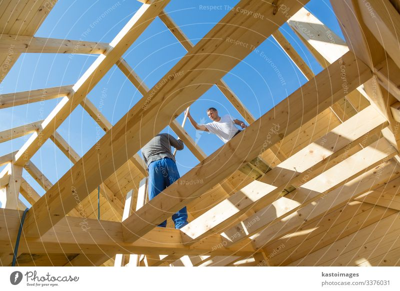 Roof builders mounting prefabricated wooden roof construction. Construction industry concept. House (Residential Structure) Work and employment Craftsperson