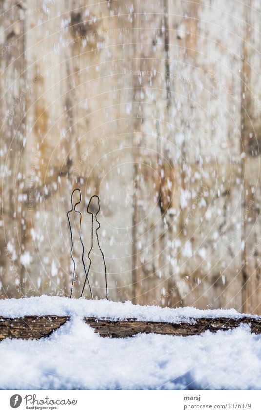 A couple is taking a walk over a snowy board in snowfall Central perspective Contrast Light Copy Space top Close-up Subdued colour Colour photo Stick figure