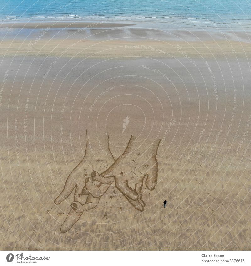 Giant sand art drawing of holding hands created by dji camera touching beach coast sustainable ecotourism environment nature Together togetherness