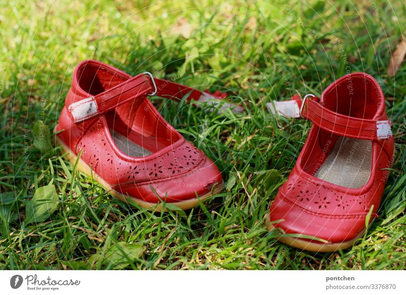 Red children's shoes in the grass Footwear ballerinas summer shoes open Velcro move out Summer Grass Green Complementary colours Barefoot Meadow Joy Lawn