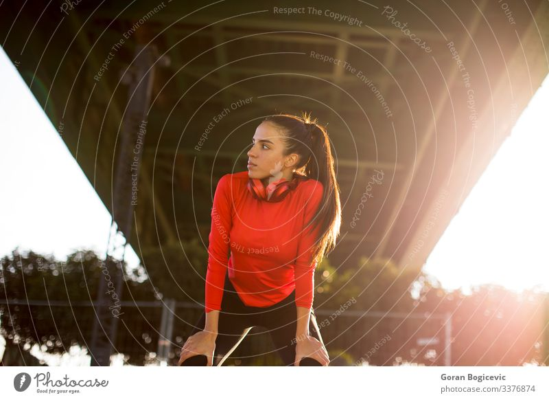 Attractive female runner taking break after jogging outdoors Lifestyle Relaxation Sports Jogging Human being Young woman Youth (Young adults) Woman Adults 1