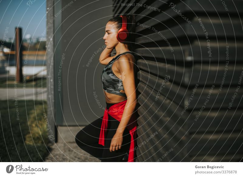 Pretty young woman takes a break after running in urban area Lifestyle Relaxation Jogging Headset Human being Young woman Youth (Young adults) Woman Adults 1