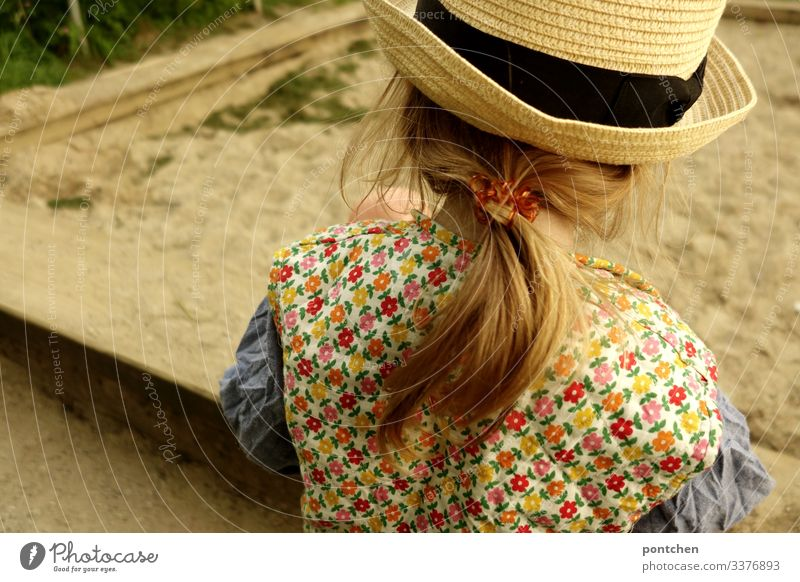 Female toddler from behind playing at the sandbox Sandpit girl Toddler Playing long hairs braid Blonde Elastic hairband Hipster Flowery pattern garments Vest