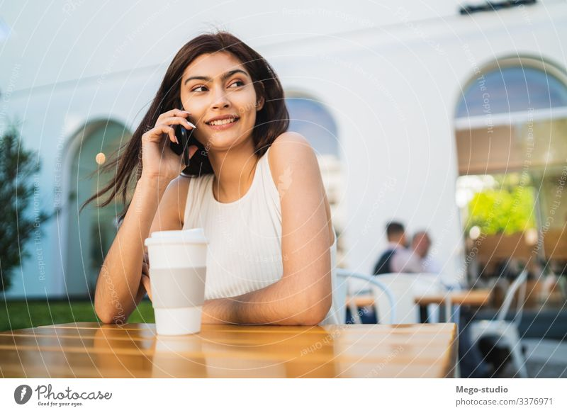 Young latin woman talking on the phone. happy mobile girl outdoor call smart cell pretty young coffee shop smartphone cellphone conversation urban people