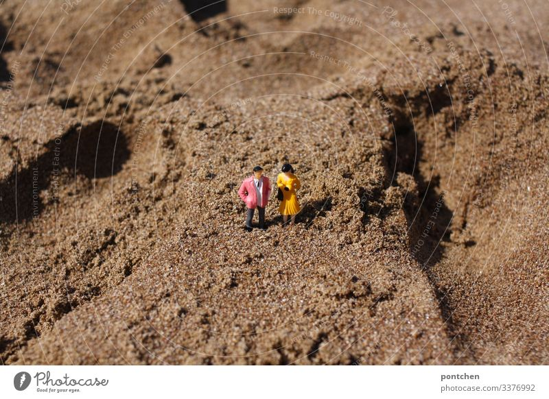 Two model figures - male and female - in the sand on the beach Couple Man Woman Beach Sand get stuck Humor bizarre Small Manikin Toys vacation Summer
