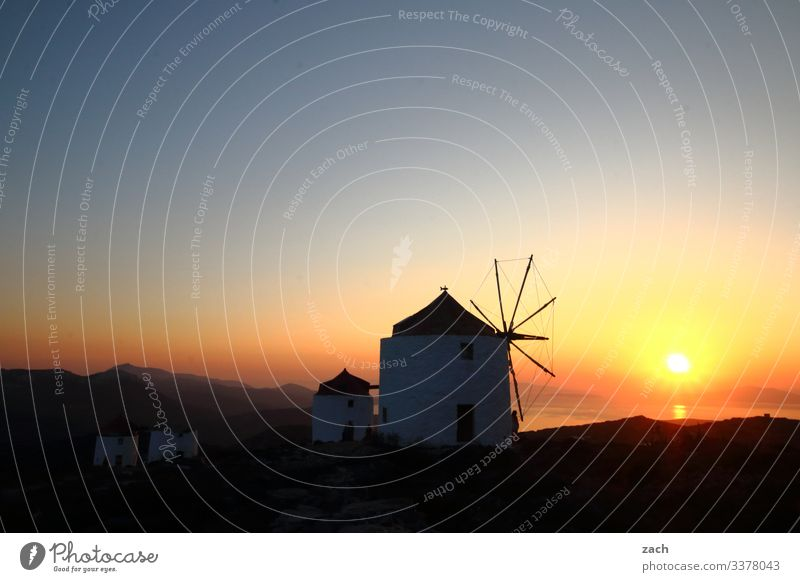 old windmills at sunset on an island in Greece the Aegean Cyclades Ocean Island Mediterranean sea Exterior shot Twilight Long exposure Deserted Copy Space top