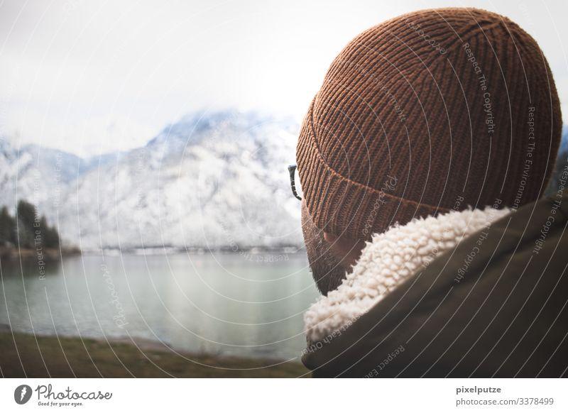Man with cap looks at mountain lake Alps Bavaria mountains Eyeglasses Nature outdoor Lake wide Winter Hiking