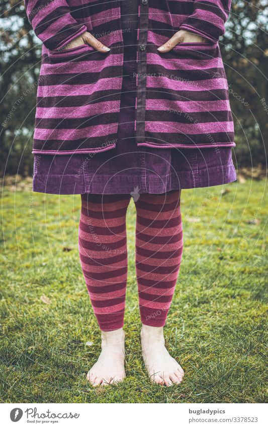 A female person stands barefoot on grass, in the background there is a hedge. The peron can be seen from chest height to the feet. She is wearing a purple striped cardigan, a purple cord skirt and pink striped leggings.