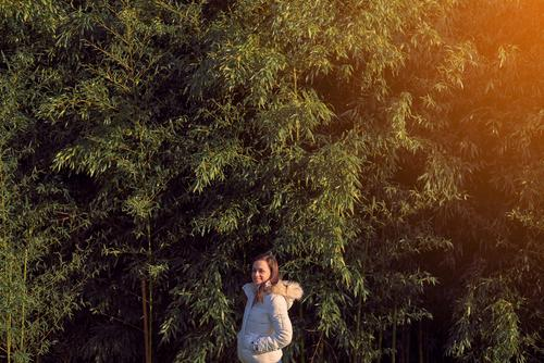 Young woman in front of a bamboo plantation young leaves green grass nature plants japanese leaf culture garden tropical background zen freshness tree asia