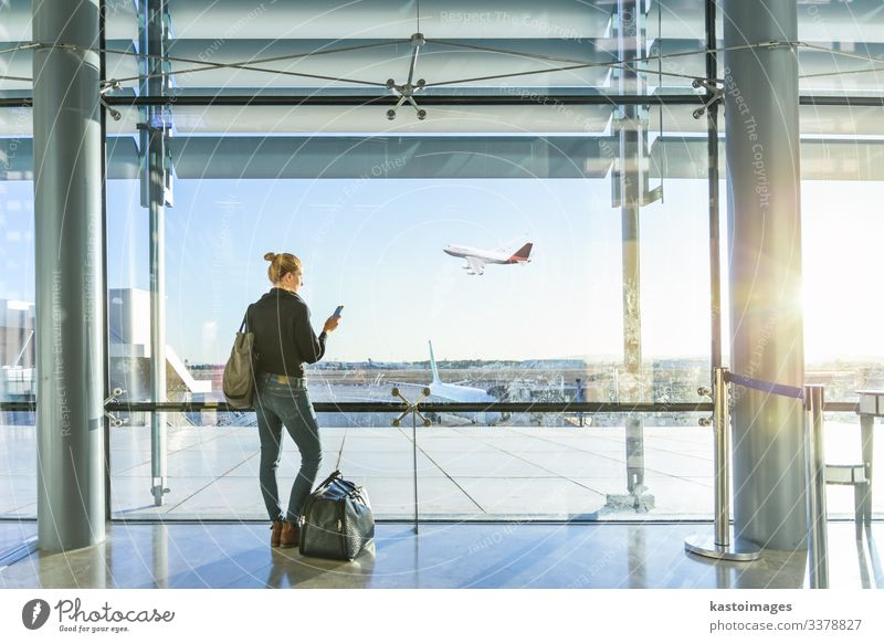 Young casual female traveler at airport, holding smart phone device, looking through the airport gate windows at planes on airport runway. Vacation & Travel