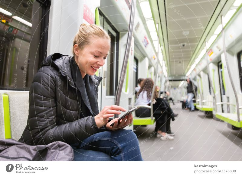 Young girl reading from mobile phone screen in metro. Lifestyle Vacation & Travel Trip Decoration Business Telephone Cellphone PDA Screen Human being Woman