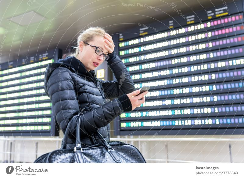 Woman at airport checking flight information on phone app. Vacation & Travel Tourism Trip Winter Decoration Telephone PDA Aviation Human being Adults Airport