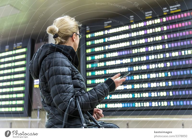 Woman at airport looking at the flight information board. Vacation & Travel Tourism Trip Winter Decoration Telephone PDA Aviation Human being Adults Airport