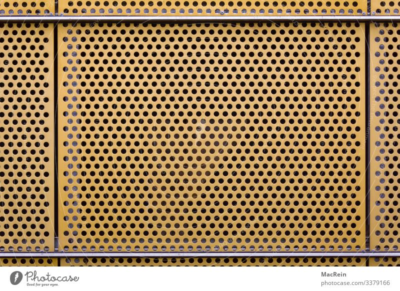 perforated sheet Metal Yellow Tin Plate with holes Wall cladding Hollow Deserted Copy Space Colour photo Exterior shot Day