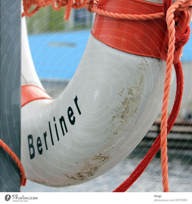 Lifebelt with the inscription Berliner hangs from a metal pole on the riverbank Life belt Ring Rescue peril Protection Rope String Help Town Capital city