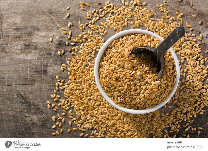 Golden flax seeds in bowl on wooden table. Top view. Copy space food cereal dry agriculture grain healthy organic brown raw barley buckwheat groats heap