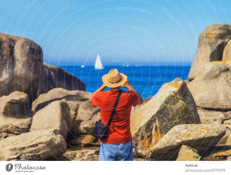Tourist with straw hat in rear view photographs a sailing ship in Brittany at the sea between rocks Joy Leisure and hobbies Take a photo Vacation & Travel