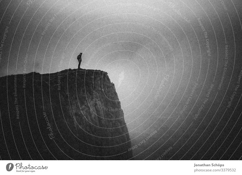 Young woman standing on a cliff in the fog Abstract Black Minimalistic Black & white photo Dark background Cliff Threat Dangerous Risk Dark gray Sombre mood