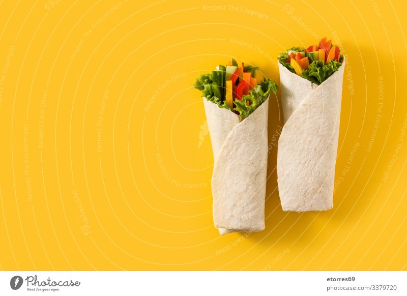 Vegetable tortilla wraps on yellow background. Top view copy space burrito carrot cucumber diet fajita food fresh green healthy isolated lettuce mexican mix