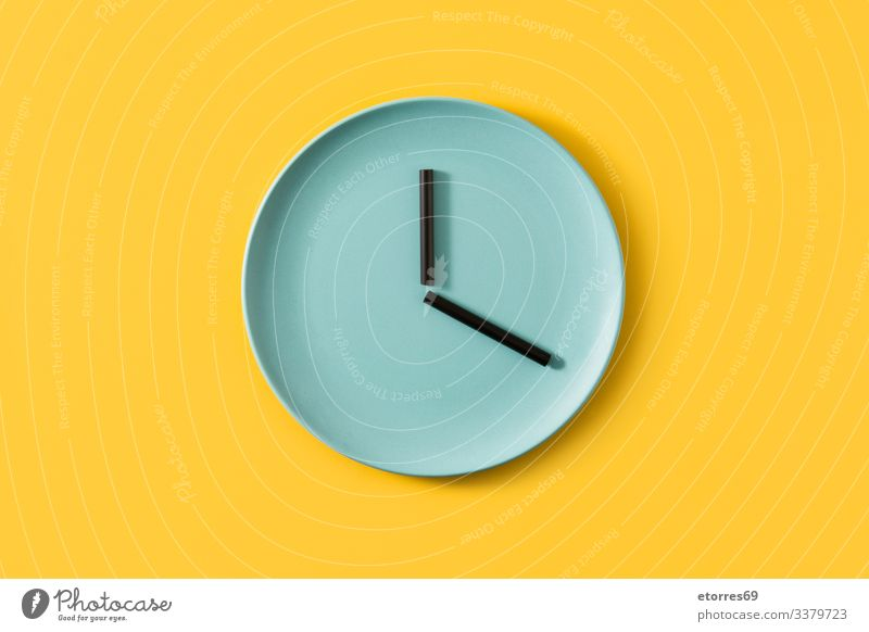 Clock made with plate and straws on yellow background clock food empty time concept kitchen kitchenware blue black eat time to eat color hour minute second Time
