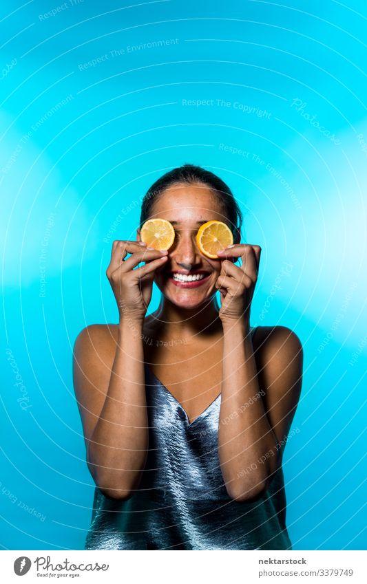 Young Woman Holding Lemon Slices on Eyes slice female girl eyes holding up concept minimalism citrus fruit fresh freshness smile happiness conceptual sky blue