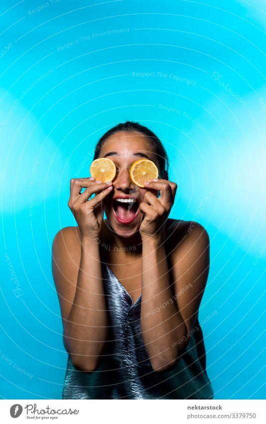 Young Woman Holding Lemon Slices Over Eyes Smiling Widely slice female girl eyes holding up concept minimalism citrus fruit fresh freshness smile happiness