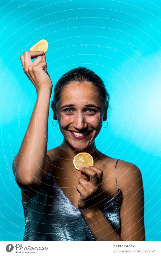 Young Woman Holding Up Lemon Slices on Blue Background lemon slice female girl holding up concept minimalism citrus fruit fresh freshness smile happiness