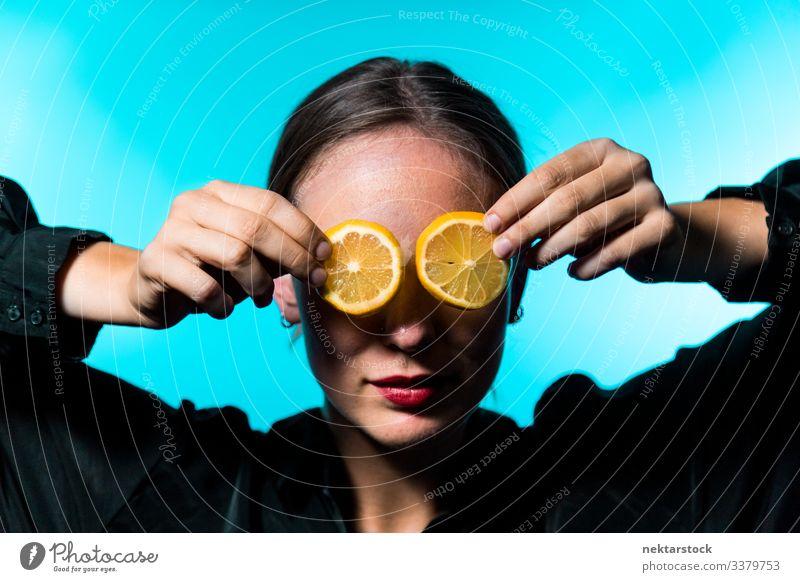 Caucasian Woman Covering Eyes with Lemon Slices on Blue Background lemon slice covering female girl eyes holding up concept minimalism citrus fruit fresh