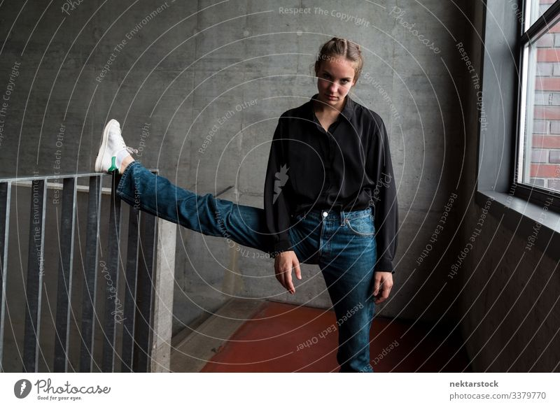 Young Woman with Leg on Staircase Handrail Looking at Camera leg handrail leg raised female girl woman stretch young adult youth culture day female beauty