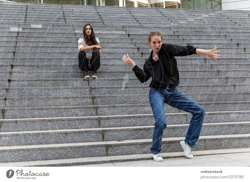 Young Woman Dancing and Another Sitting on Marble Steps sitting dancing females girl steps staircase women young adult youth culture day urban female beauty