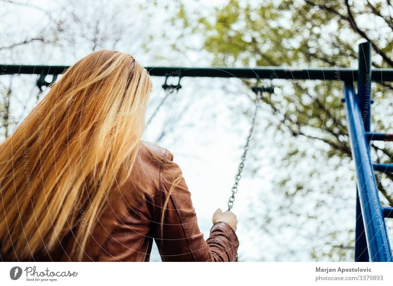 Young woman on a swing on a playground Lifestyle Joy Freedom Human being Feminine Youth (Young adults) Woman Adults 1 30 - 45 years To enjoy To swing Happiness