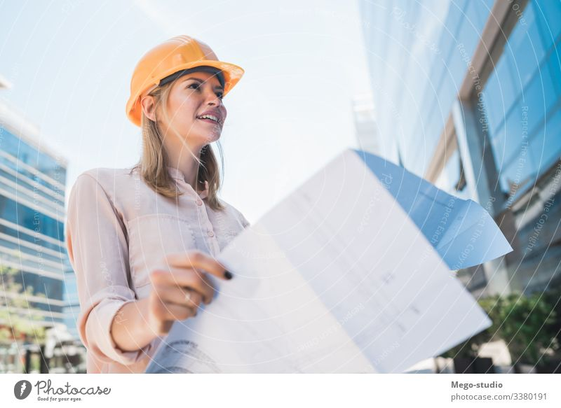 Professional architect holding blueprints outdoors. woman professional engineer business architecture consultant urban builder working city employee protective