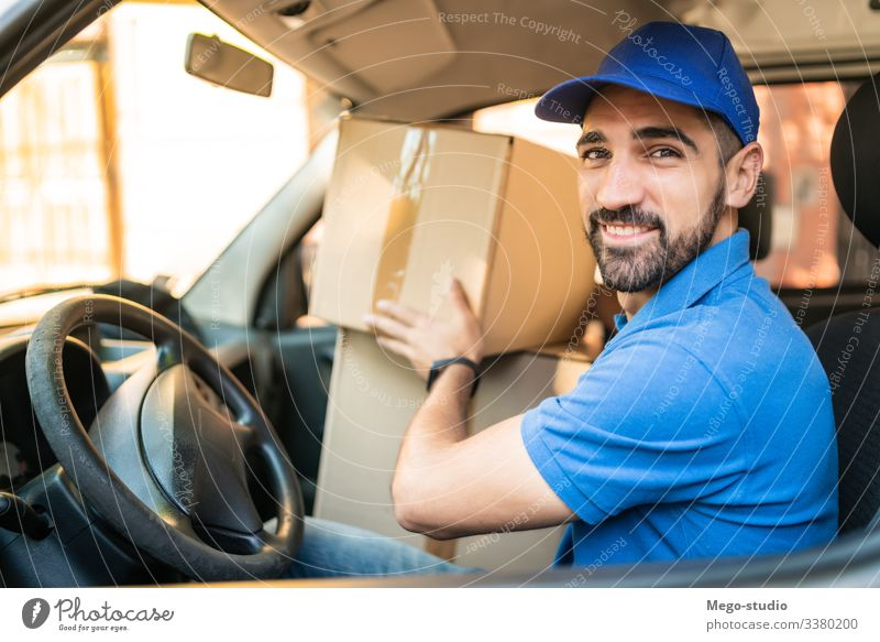 Delivery man driving van with cardboard boxes on seat. male service package delivery shipping industry work send office closeup logistic consumer carrying
