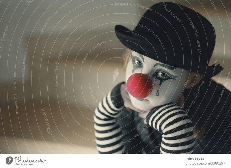 Die Tränen des Clowns Fasching traurig trauriger Clown Hut Schwarz gestreift clownnase rote nase schminke melancholie trauer nachdenklich gedanken sitzen