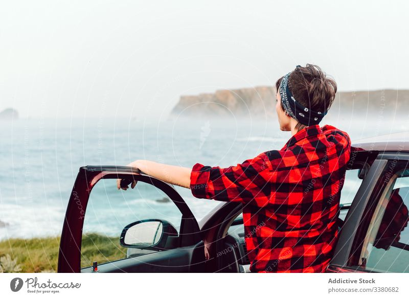 Female teenager in casual wear at lonely seashore woman extraordinary travel view seaside shirt rebel female hipster car transport trip journey nature vehicle