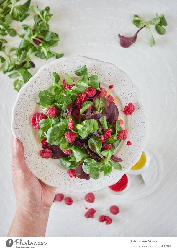 Person holding plate with raspberry and spinach salad cook fresh organic sweet delicious tasty natural green vegetarian healthy diet food leave dessert plant