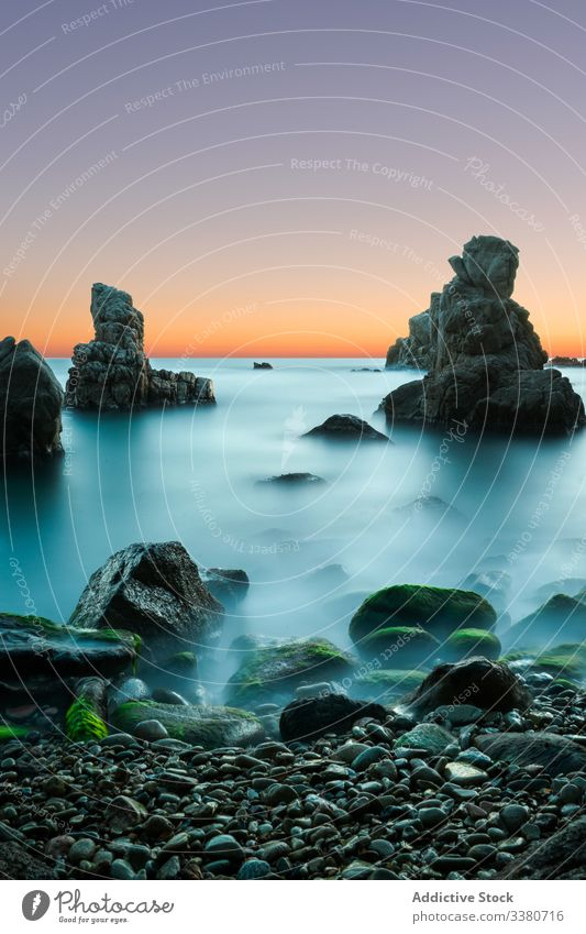 Amazing sunset above rocky seashore in mist landscape long exposure sky nature colorful blue turquoise cliff marine beach water stone scenic tranquil coast