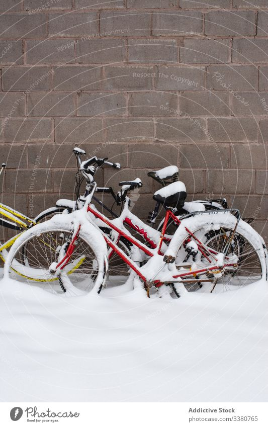 Covered with snow bicycles next to stone wall winter bike street transport colorful vehicle travel exterior building tourism swedish lapland norrbotten north