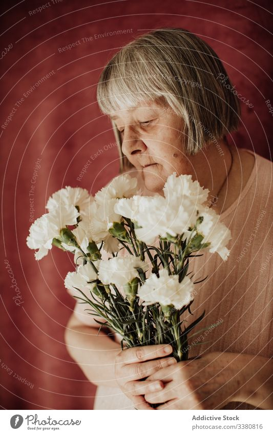 Pensive elderly woman with flowers at home old carnation bouquet floral natural gift fresh female spring celebrate fragrant event holiday festive peaceful