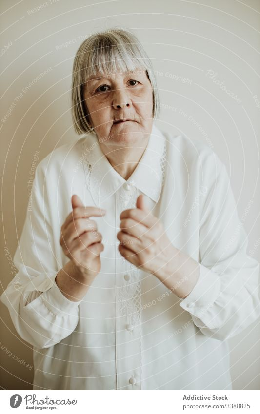 Old woman gesturing in studio old gesture elderly show rise hands senior home female pensioner serious natural blouse contemporary sign event festive