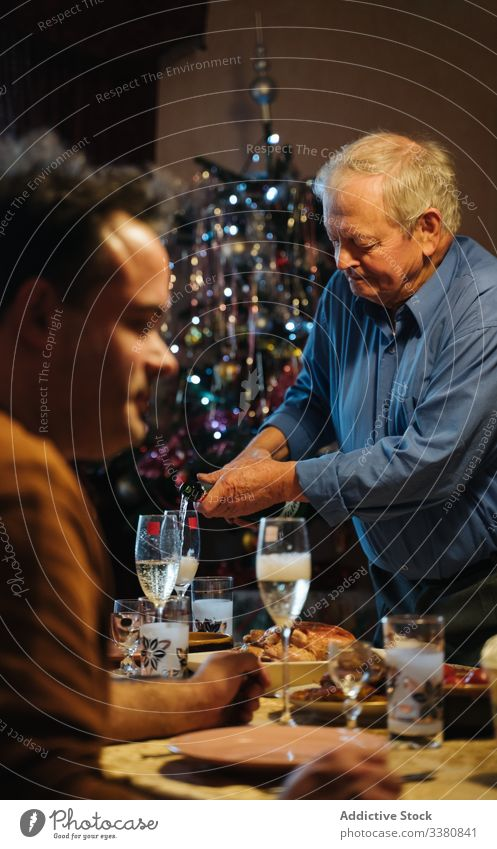 Old man pouring champagne in glasses during Christmas dinner at home christmas celebrate bottle aged senior casual drink beverage male alcohol lifestyle