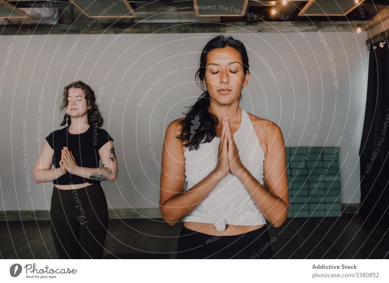 Barefooted women practicing yoga in mountain pose meditation practice namaste relax class training calm focus people samasthiti athletic exercise healthy