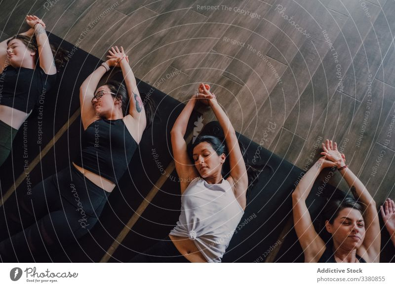 Tranquil athletes practicing yoga together performing corpse pose in contemporary workout room relax exercise savasana tranquil meditate breath idyllic studio