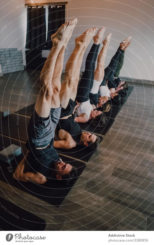 Focused athletes practicing yoga together performing supported shoulderstand balance position in contemporary gym gymnastic stretch exercise training leg