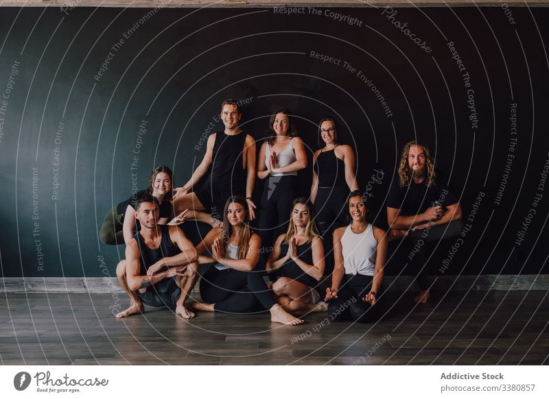 Group of joyful athletes in various yoga poses in contemporary workout room class balance practice happy training studio namaste club stretch people smile