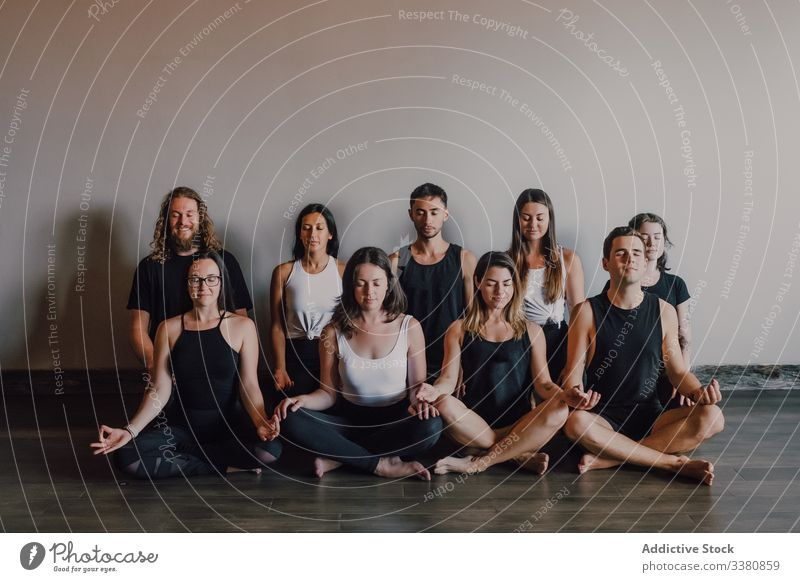 Group of calm relaxed athletes practicing yoga together performing lotus pose in light modern workout room meditate gyan mudra training serene peaceful