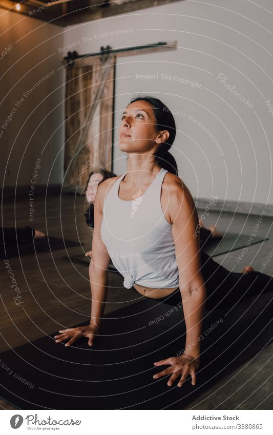 Woman practicing yoga in upward facing dog pose woman athletic position practice stretch class training flexible exercise body sportswear healthy workout hatha
