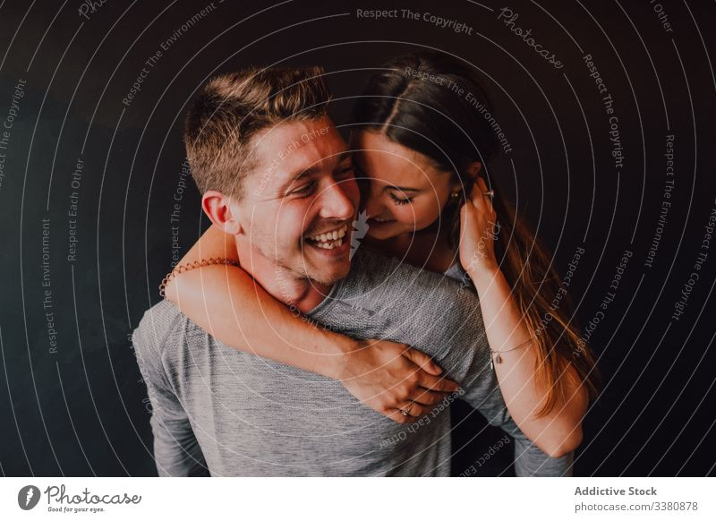 Cheerful couple having fun while relaxing together after training in dark modern fitness studio laugh cheerful piggyback enjoy flirt love hug athlete embrace